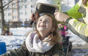 Glückliches Mädchen auf Quad mit Helm im Winter