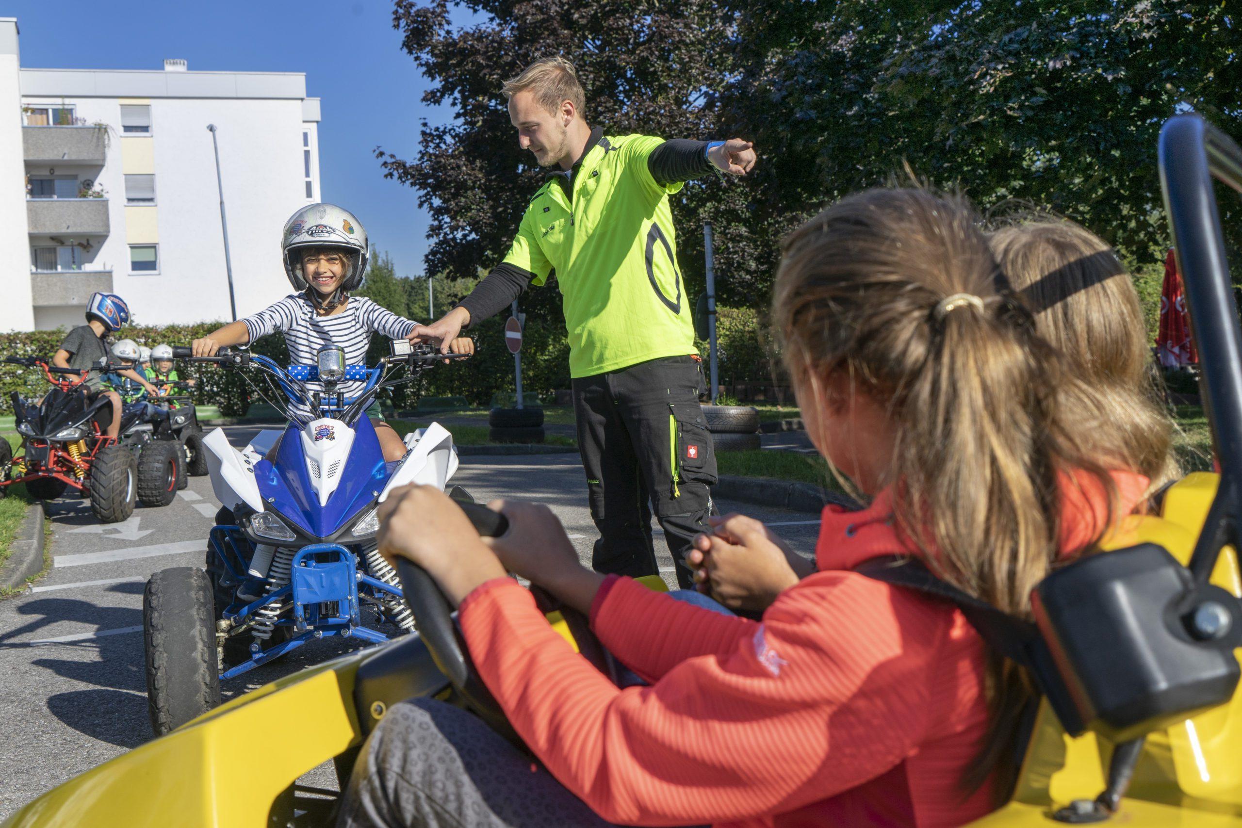 Quad und Kinderauto mit Verkehrshelfer