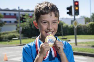 Kind mit goldener Medaille vor Ampel