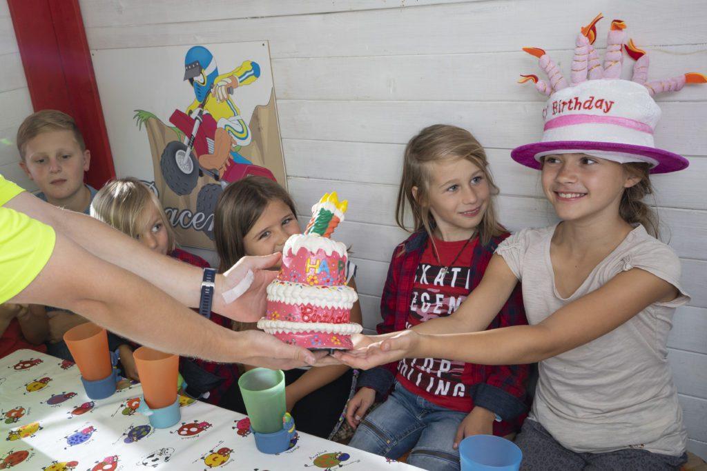 Geburtstagstorte wird dem Geburtstagskind überreicht.